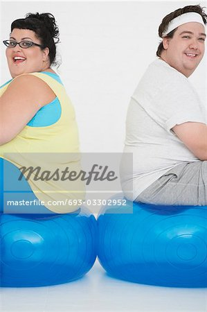 Overweight man and woman sitting back to back on exercise balls, portrait Stock Photo - Premium Royalty-Free, Image code: 693-03302952