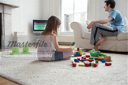 Girl (5-6) sitting on floor, playing with blocks, father watching television Stock Photo - Premium Royalty-Free, Image code: 693-03305063