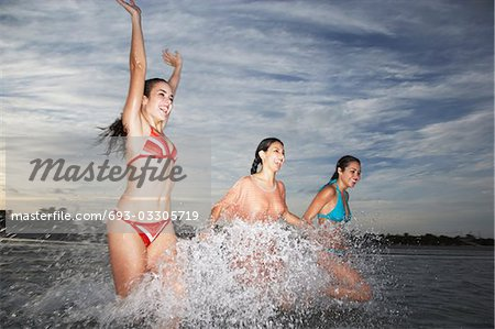 Three teenage girls (17-19) splashing in sea Stock Photo - Premium Royalty-Free, Image code: 693-03305719