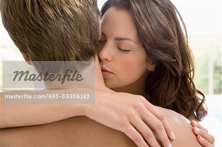 Woman kissing man's neck, head and shoulders Stock Photo - Premium Royalty-Free, Image code: 693-03306183