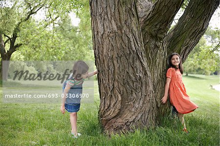 Two girls (7-9) playing hide and seek by tree Stock Photo - Premium Royalty-Free, Image code: 693-03306970