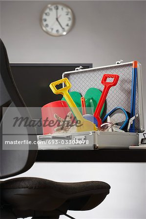 Beach toys in open business case in office Stock Photo - Premium Royalty-Free, Image code: 693-03307078