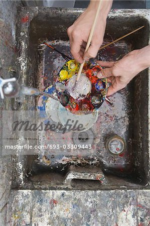 Artist rinsing palette at sink in studio, view from above, close-up of hands Stock Photo - Premium Royalty-Free, Image code: 693-03309443