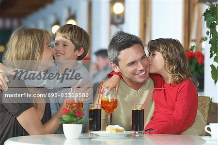 Parents and children (7-9) with drinks, embracing at restaurant Stock Photo - Premium Royalty-Free, Image code: 693-03309580
