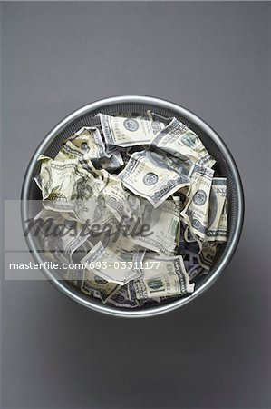 Dollar bills in wastebasket, view from above Stock Photo - Premium Royalty-Free, Image code: 693-03311177