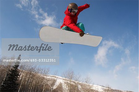 Teenage snowboarder jumping Stock Photo - Premium Royalty-Free, Image code: 693-03312351