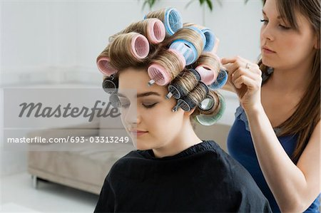 Hairstylist Rolling Hair of Model Stock Photo - Premium Royalty-Free, Image code: 693-03313249