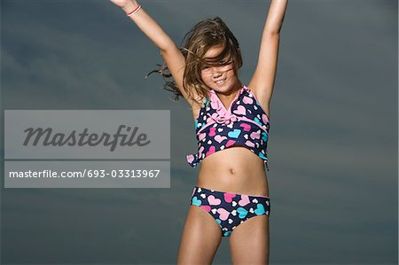 Little Girl in a Swimsuit Jumping Stock Photo - Premium Royalty-Free, Image code: 693-03313967