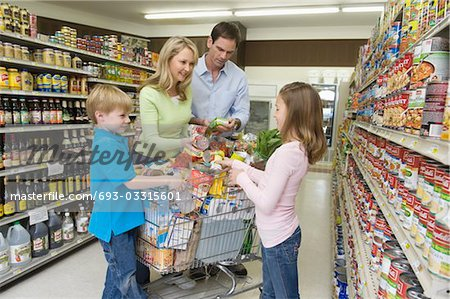 Family of four shopping in supermarket Stock Photo - Premium Royalty-Free, Image code: 693-03315601
