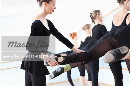 Ballet teacher adjusting foot position at the barre Stock Photo - Premium Royalty-Free, Image code: 693-03317846