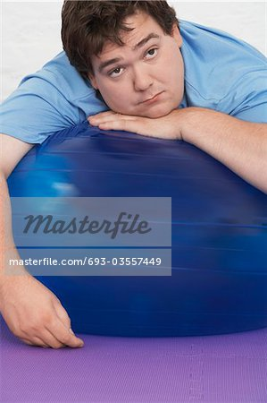 Overweight Man Resting on Exercise Ball, portrait Stock Photo - Premium Royalty-Free, Image code: 693-03557449