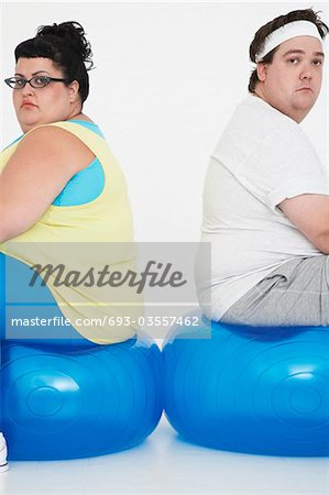 Unhappy overweight man and woman sitting back to back on exercise balls, portrait Stock Photo - Premium Royalty-Free, Image code: 693-03557462