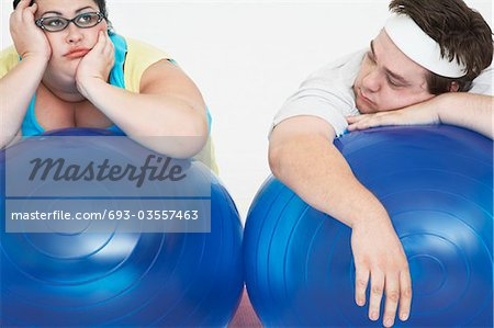 Disinterested overweight man and woman lying on Exercise Balls, close up Stock Photo - Premium Royalty-Free, Image code: 693-03557463