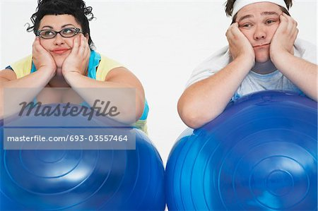 Disinterested overweight man and woman lying on Exercise Balls, close up Stock Photo - Premium Royalty-Free, Image code: 693-03557464