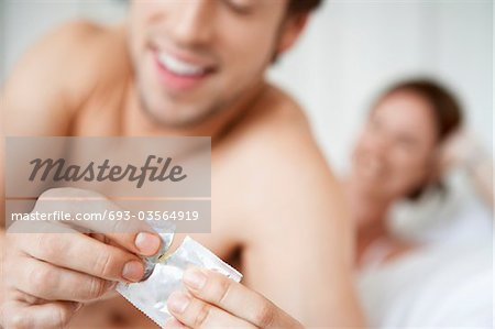 Couple in bed, man opening condom, close up of condom Stock Photo - Premium Royalty-Free, Image code: 693-03564919