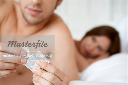 Couple in bed, man opening condom, close up of condom Stock Photo - Premium Royalty-Free, Image code: 693-03564920