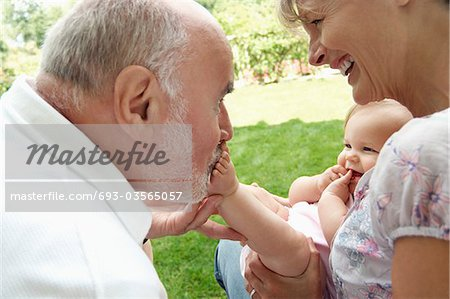 Grandparents playing with granddaughter in garden Stock Photo - Premium Royalty-Free, Image code: 693-03565057