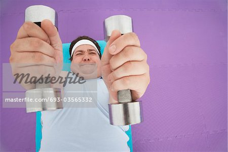Overweight Man lying down Lifting dumbbells, overhead view Stock Photo - Premium Royalty-Free, Image code: 693-03565332