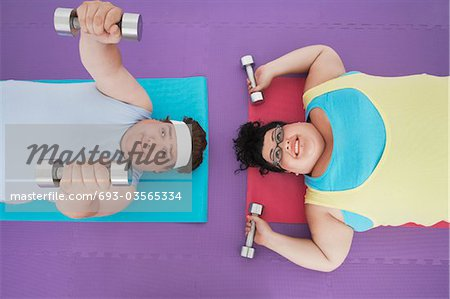 Overweight man and woman lying down lifting dumbbells, overhead view Stock Photo - Premium Royalty-Free, Image code: 693-03565334