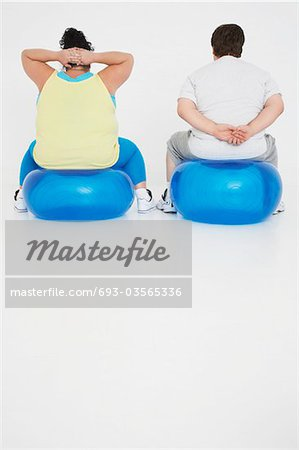 Overweight man and woman Exercising on exercise Balls, back view Stock Photo - Premium Royalty-Free, Image code: 693-03565336