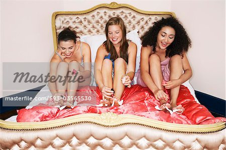 Teenage Girls in pyjamas painting toenails on funky bed at slumber party