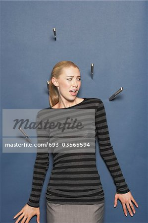 Woman surrounded by thrown knives against blue background Stock Photo - Premium Royalty-Free, Image code: 693-03565594