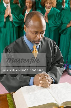 Preacher by altar in church Bowing Head in Prayer, high angle view Stock Photo - Premium Royalty-Free, Image code: 693-03686347