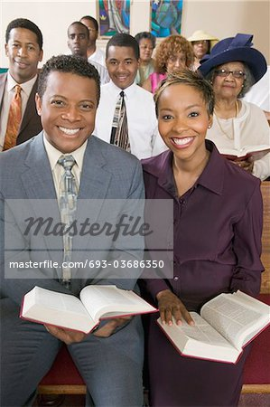 Young couple with Bibles sitting on church pews, portrait Stock Photo - Premium Royalty-Free, Image code: 693-03686350