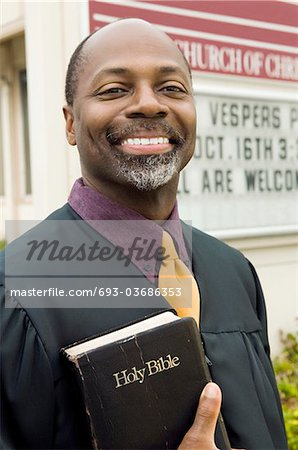 Smiling Preacher in Front of Church, portrait Stock Photo - Premium Royalty-Free, Image code: 693-03686353