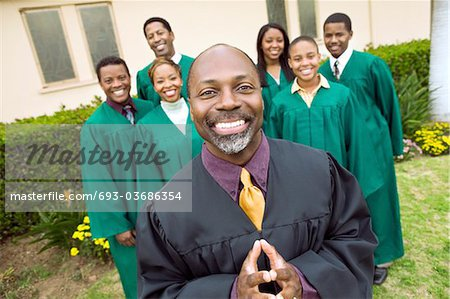 Minister in church garden, gospel choir in background, portrait Stock Photo - Premium Royalty-Free, Image code: 693-03686354
