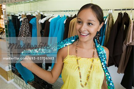 Girl Trying on Sequin Boa in clothing store Stock Photo - Premium Royalty-Free, Image code: 693-03706983