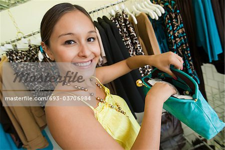 Girl Looking at Purse in Boutique, portrait Stock Photo - Premium Royalty-Free, Image code: 693-03706984