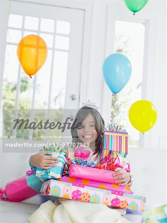 Portrait of young girl (7-9) with birthday presents, smiling Stock Photo - Premium Royalty-Free, Image code: 693-03707929