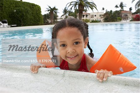 Girl (5-6 years) holding on to edge of swimming pool Stock Photo - Premium Royalty-Free, Image code: 693-03707931