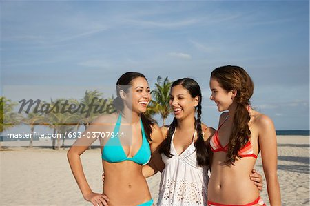 Three teenage girls (16-17) wearing bikinis, standing on beach, portrait Stock Photo - Premium Royalty-Free, Image code: 693-03707944