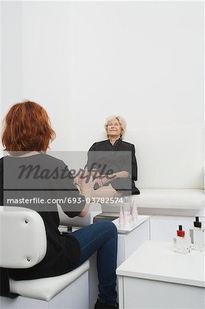 Foot masseuse and client in Palm Springs salon Stock Photo - Premium Royalty-Free, Image code: 693-03782574