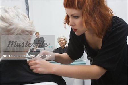Stylist makes finishing touches to elderly woman's hair Stock Photo - Premium Royalty-Free, Image code: 693-03782597