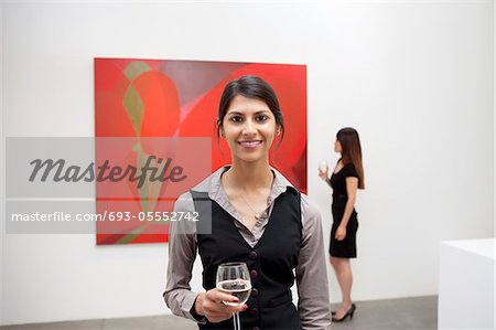 Portrait of young woman in front of painting in art gallery Stock Photo - Premium Royalty-Free, Image code: 693-05552742