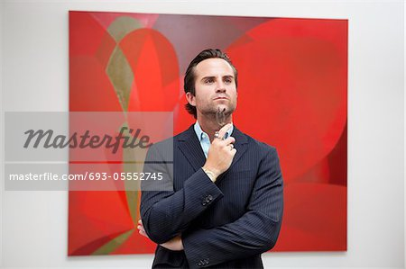 Young adult man thinking in front of painting in art gallery Stock Photo - Premium Royalty-Free, Image code: 693-05552745