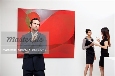 Young man thinking with two women talking in background in art gallery Stock Photo - Premium Royalty-Free, Image code: 693-05552746
