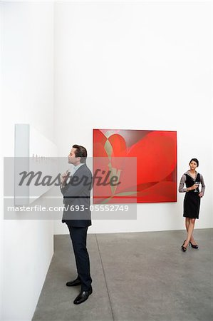 Full length of man standing in front of wall painting and woman Stock Photo - Premium Royalty-Free, Image code: 693-05552749