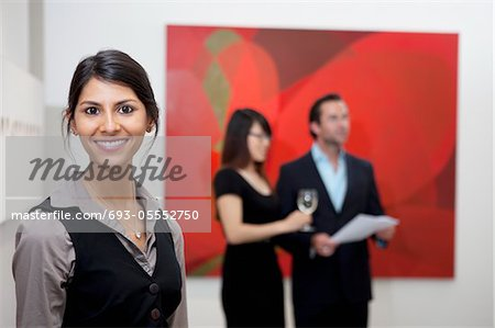 Portrait of smiling young woman in front of a couple in art gallery Stock Photo - Premium Royalty-Free, Image code: 693-05552750