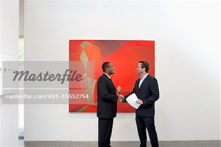 Two people shaking hands in front of wall painting Stock Photo - Premium Royalty-Free, Image code: 693-05552754