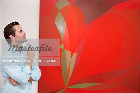 Thoughtful young man looking at painting in art gallery Stock Photo - Premium Royalty-Free, Image code: 693-05552760