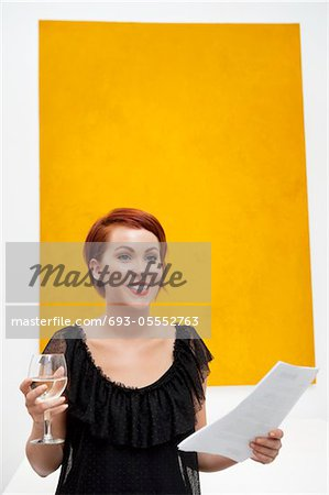 Smiling young woman in front of yellow wall painting Stock Photo - Premium Royalty-Free, Image code: 693-05552763