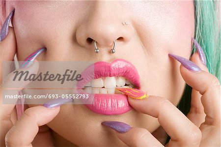 Close-up of a woman's mouth and fingers Stock Photo - Premium Royalty-Free, Image code: 693-05552793