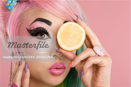 Portrait of a woman holding slice of lime in front of her eyes Stock Photo - Premium Royalty-Free, Image code: 693-05552794