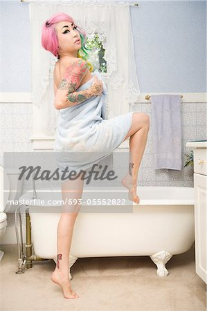 Young woman in towel posing in front of bathtub Stock Photo - Premium Royalty-Free, Image code: 693-05552822