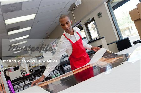 Manual worker taking large printouts Stock Photo - Premium Royalty-Free, Image code: 693-05794020