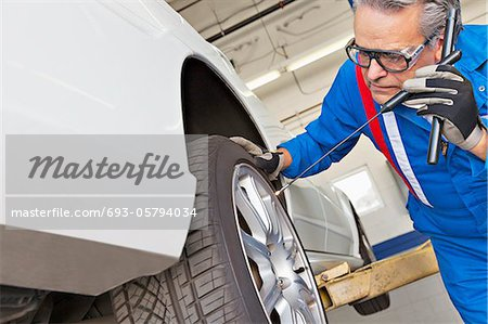 Elderly man working on car tire Stock Photo - Premium Royalty-Free, Image code: 693-05794034